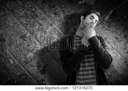 Portrait of man shaving with straight edge razor against wooden floor