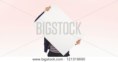 Man holding billboard in front of face against beige