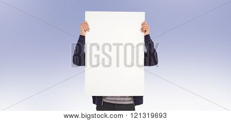 Man showing billboard in front of face against purple