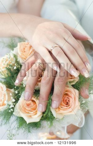 Wedding bouquet from pastel pink roses, hands and rings