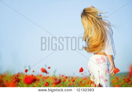Blond girl with beautiful long hair in field of poppies in summer