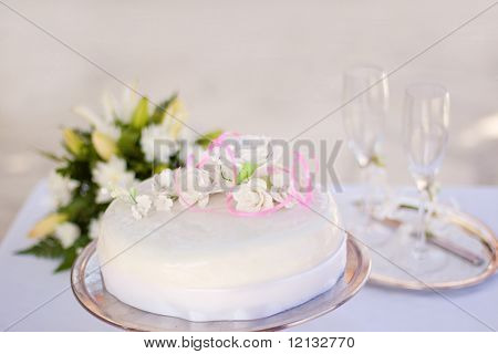 Wedding cake with blurred wineglasses