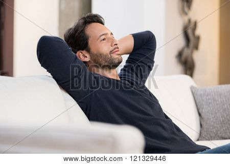 Portrait of a young man resting on sofa and thinking about the future. Handsome young man with hands behind head sitting on couch in living room. Positive man daydreaming and relaxing at home.