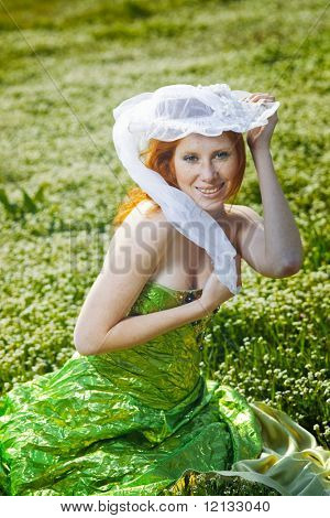 Redheaded girl in hat posing on spring field