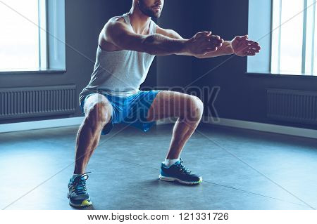 Deep squat. Part of young man in sportswear doing squat at gym
