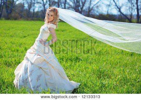 Beautiful bride posing on fresh green grass