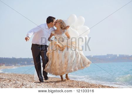 Wedding couple running and kissing on sea coast