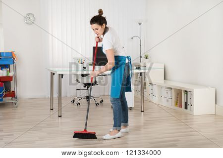 Female Janitor Sweeping Floor With Broom