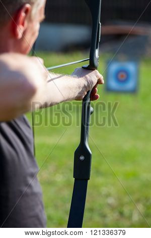 Man aiming bow at target outdoors