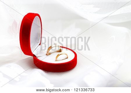 two wedding rings in red case on white abstract background