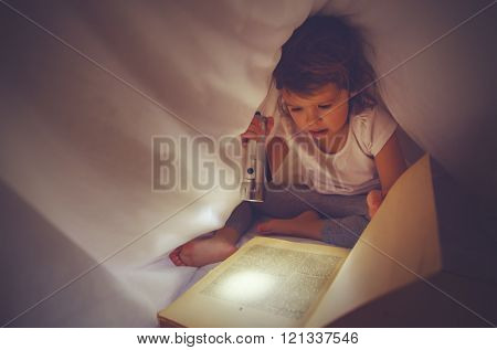 Child Girl Reading  Book In Dark, Under Covers In Bed With Light Of Flashlight