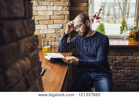 a young man with glasses, beard, sitting in cafe and reading a book