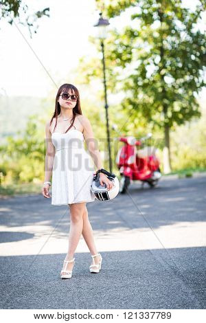 Portrait of happy young woman with black and white helmet in hands near red scooter. Defocused backg