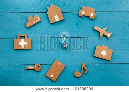 Cardboard web icons  and light bulb on blue background