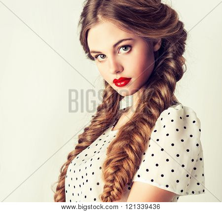Beautiful girl model with hair in two long braids .Polka dot dress and hairstyle pigtails