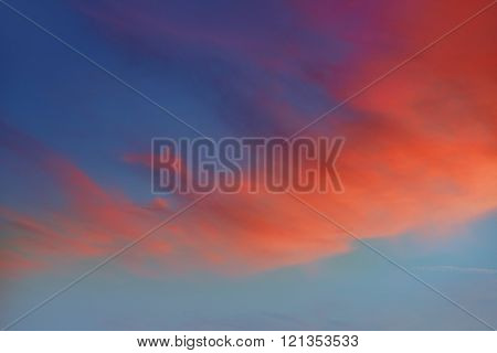 Red orange clouds in dramatic sunset blue sky