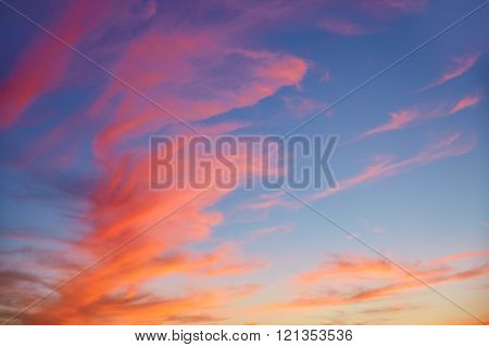 Red orange clouds at sunset over blue sky