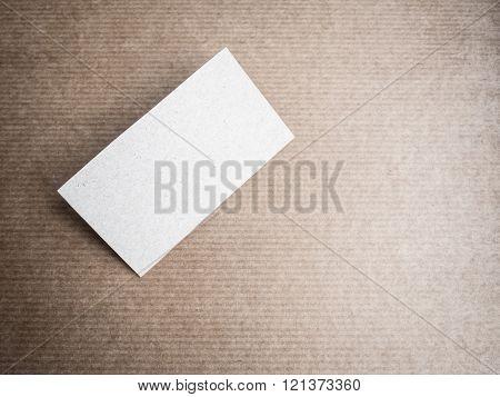 Blank cardboard business card mockup on kraft hardboard background