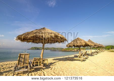 A row of wooden lounge with direct sunlight at Lombok beach Indonesia