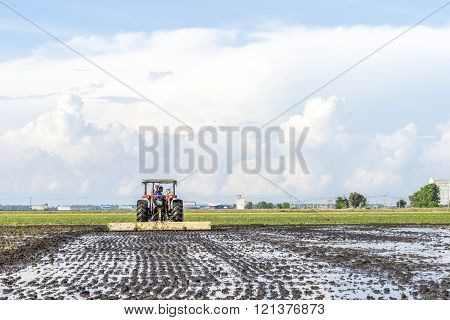 SELANGOR MALAYSIA - JANUARY 31 2016: Worker uses a machine to tilling the soil for planting rice on paddy field in Sekinchan Malaysia. Sekinchan is one of the major rice supplier in Malaysia.