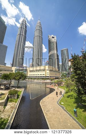 KUALA LUMPUR MALAYSIA - JANUARY 10 2016: Tourists visit the KLCC park which contains the Petronas Towers and luxury hotels and shopping mall in Kuala Lumpur