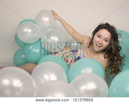 beautiful curly girl in a  multi-colored dress playing with balloons