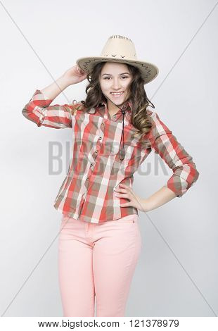 beautiful curly girl in pink pants, a plaid shirt and cowboy hat.