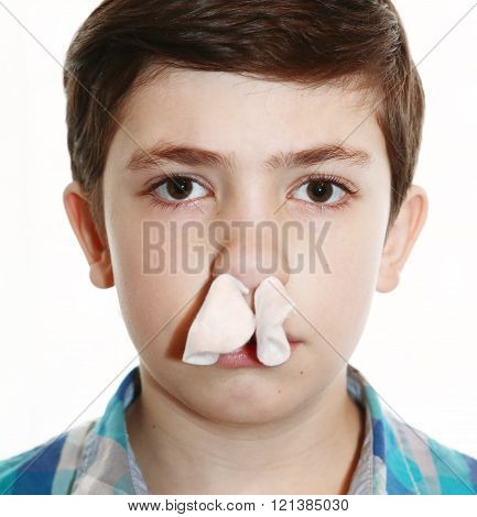 preteen handsome boy with dark brown hair has nasal bleeding with tampon in the nostrils close up portrait isolated on white