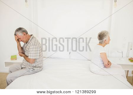 Annoyed couple ignoring each other in the bedroom