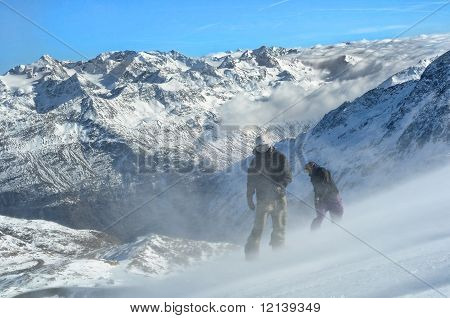 Two Snowboarders On Steep Slope In Very Windy Conditions.