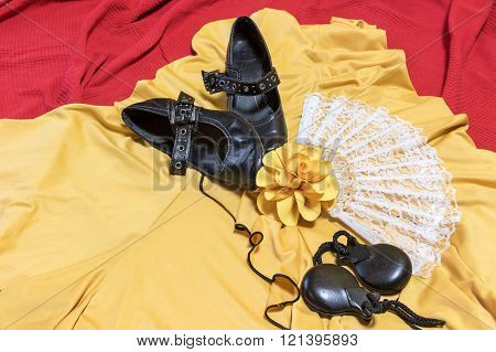 Aerial view of assesories for Flamenco dance. Black shoes, yellow rose, white fan and castanets are lying on a yellow clothes and red underlay.