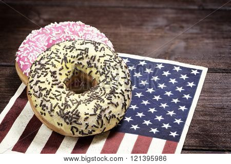 Pink and yellow american donuts are lying on the napkin in american flag desig. Photo is edited as vintage with dark edges.