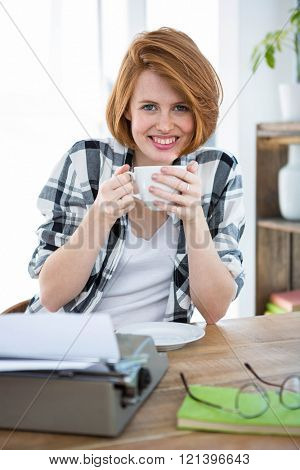 smilin hipster woman sitting at her desk drinking coffee