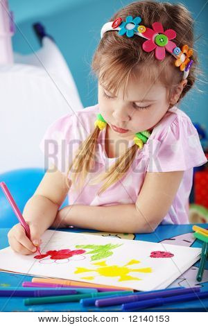 Child painting in her nursery at home