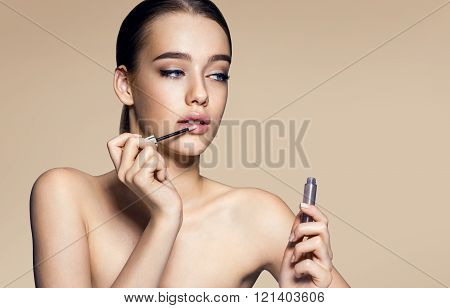 Tempting young woman with lip gloss