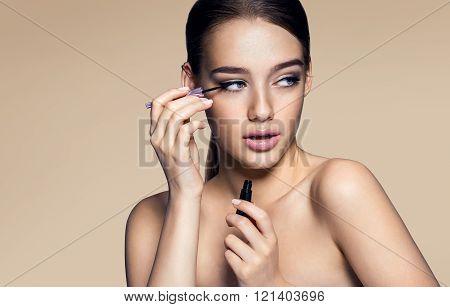 Seductive young woman applying eyeliner.