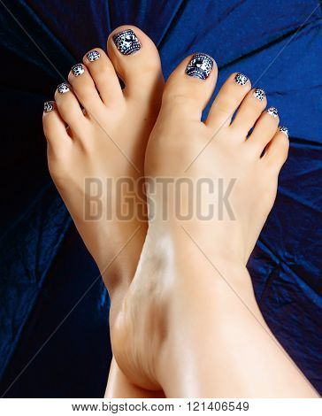 Female legs pedicure close up view. Nail painting. Delicate winter pedicure. Drawing on nails. Beautiful well-groomed feet with pedicure and varnish on nails and artistic painting.