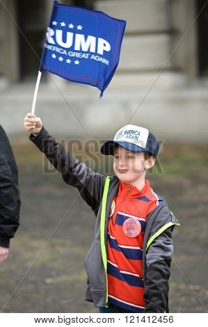Saint Louis, MO, USA - March 11, 2016: Young Donald Trump supporter holds signs rally outside the Peabody Opera House in Downtown Saint Louis