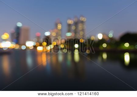 Night view blurred bokeh lights city downtown and water reflection