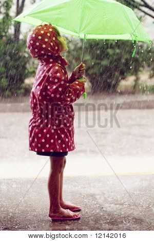 Little child walking in the rain