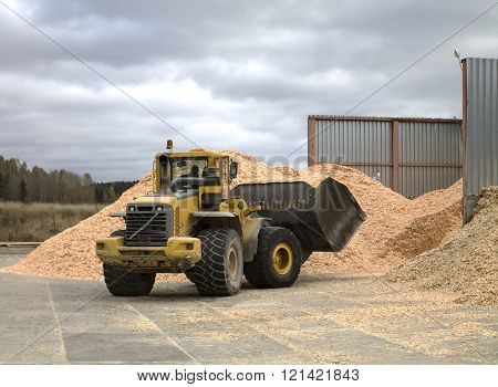 Front Loader By The Pile Of Sawdust