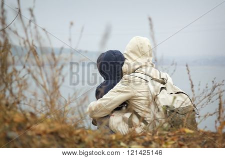 Mom and child in jackets with hood on the lake
