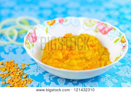 Yellow Pease Porridge With Carrots And Onions In A White Plate On  A Blue Background