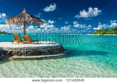 Two beach chairs under umbrella with ocean view in tropical Maldives