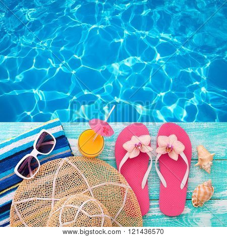 Summer Holidays in Beach Seashore. Summer drinks. Summer rest. Fashion accessories summer flip flops, hat, sunglasses on bright turquoise board near the pool poster