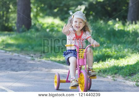 Two year-old laughing girl wearing corduroy flat cap and polka-dotted costume cycling kids pink and