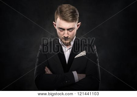 Elegant young man in suit looking frowning.