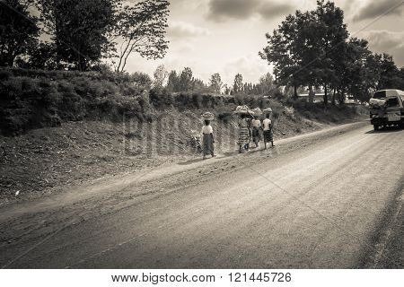 MOSHI/TANZANIA - JANUARY 16, 2016: Black Weman With Bags On The Heads Go Straight the road