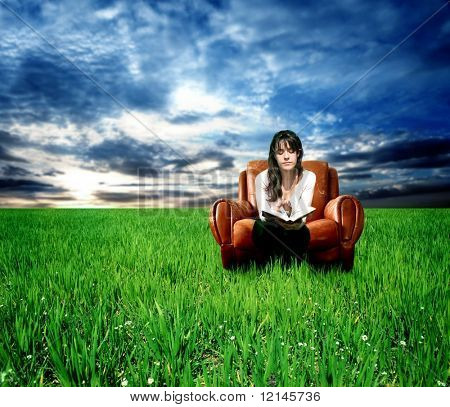 a woman on the arm-chair on the grass field