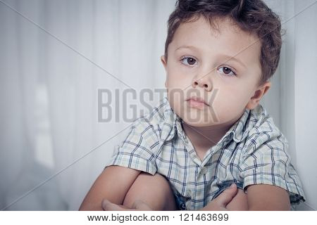 Portrait Of Sad Little Boy Sitting Near The Window At Home
